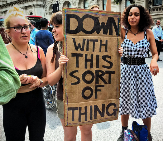 "scene of a protest with a woman holding a sign that says ""Down with this sort of thing"""