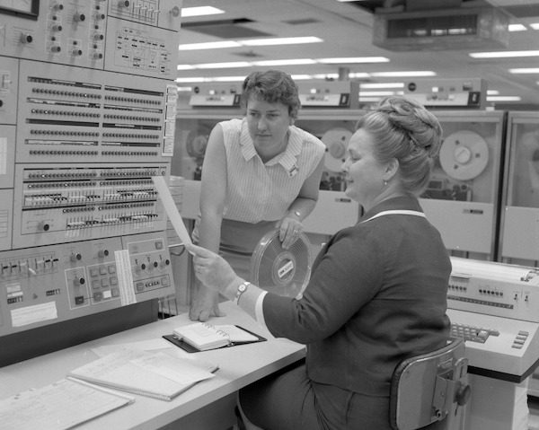image of two women looking at soimething in front of on older mainframe. Black and white image