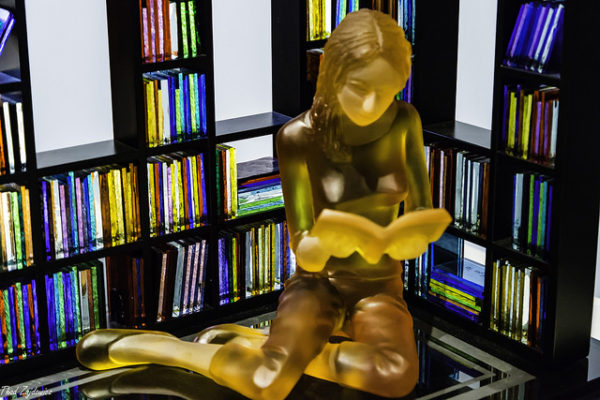 Image of a glass statue of a woman who appears to be reading a book in front of a bunch of illuminated glass books