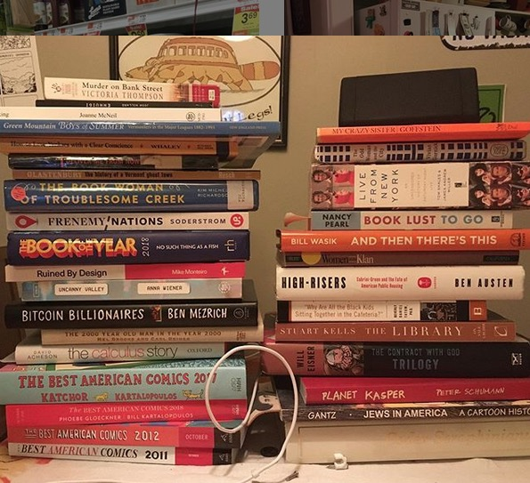 double pile of books on my kitchen table, some of which were there this time last year.