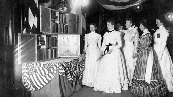 a bunch of women in victorian era dresses standing around some travelling libraries