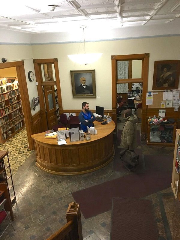 a view of the library from the top of the stairs showing a gorgeous circular reference desk with a librarian talking with a patron