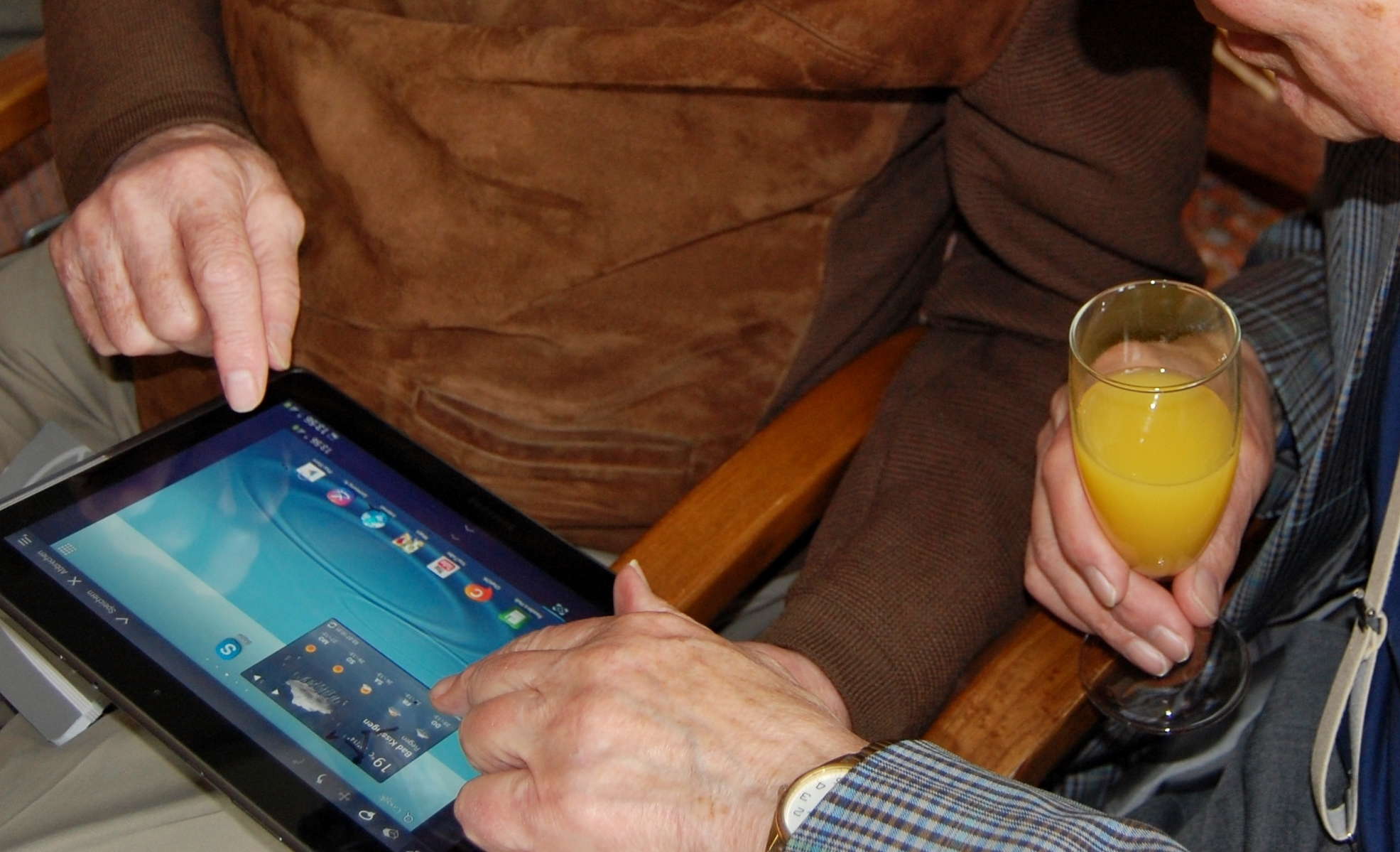 hands of two men using a tablet computer