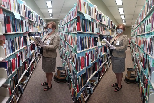 two shots of a woman reading books in a library stacks aisle with her mask on, In oe of the shots she is looking at the book, in another she is looking at the camera